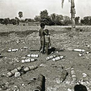 Two displaced and poverty-stricken children stand in an open field surrounded by used artillery shells in a village in former war-torn East Pakistan (1971).