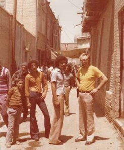 European tourist with two students of the Peshawar University in an old street of Peshawar (1974).