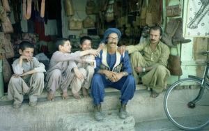 A western tourist dressed like a local poses with a group of Pushtun children (and a man) outside a shop in the Bara area of Khyber Pakhtunkhwa (1975).
