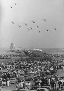Crowds gather at a runaway at the Karachi Airport to witness a 'flying parade' and joint military exercises of American and Pakistani armed forces (1953).