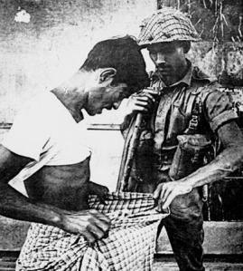 An intriguing June 1971 photograph of a West Pakistani soldier searching an East Pakistani Bengali in Dhaka (the former capital of East Pakistan).  –Picture courtesy LIFE.