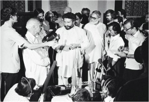 late Pir Pagara talking to the press at the Karachi Press Club in 1977. Pagara was heading a right-wing movement against the Z. A. Bhutto regime. Here he is seen talking to the press (surrounded by some members of the Jamat-i-Islami, Jamat Ulema Islam and Jamiat Ulema Pakistan). The men then got up to say their evening prayers. However, a commotion broke out between the religious leaders of the movement when JI and JUI men refused to pray behind JUP leader, Shah Noorani. JUI was inclined towards Sunni Deobandi school of thought whereas Noorani was from the pro-Barelvi JUP. Though united in their opposition to Bhutto's 'socialism', both men thought the other was a 'misguided Muslim.